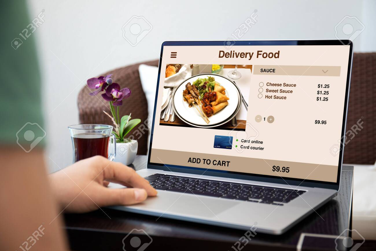 male hands on laptop keyboard with food delivery application on the screen - 147610027