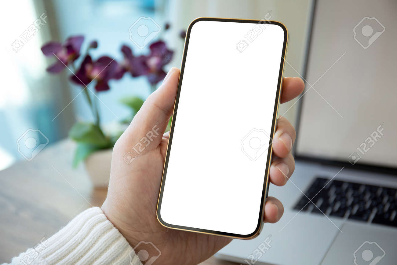 Man hands holding golden phone with isolated screen over white table in office - 167945710