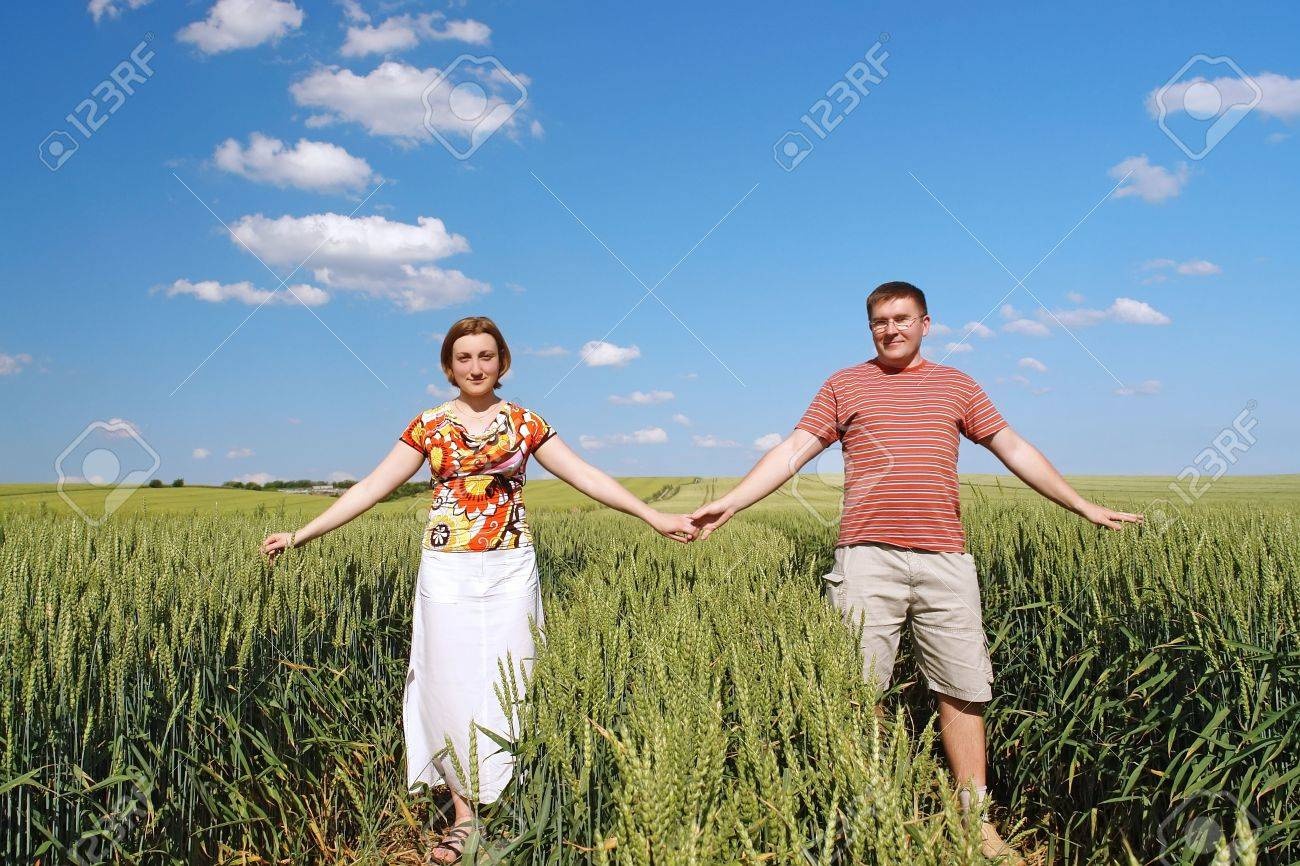 Young couple holding each other with hands posing happily in cornfield Stock Photo - 1091532