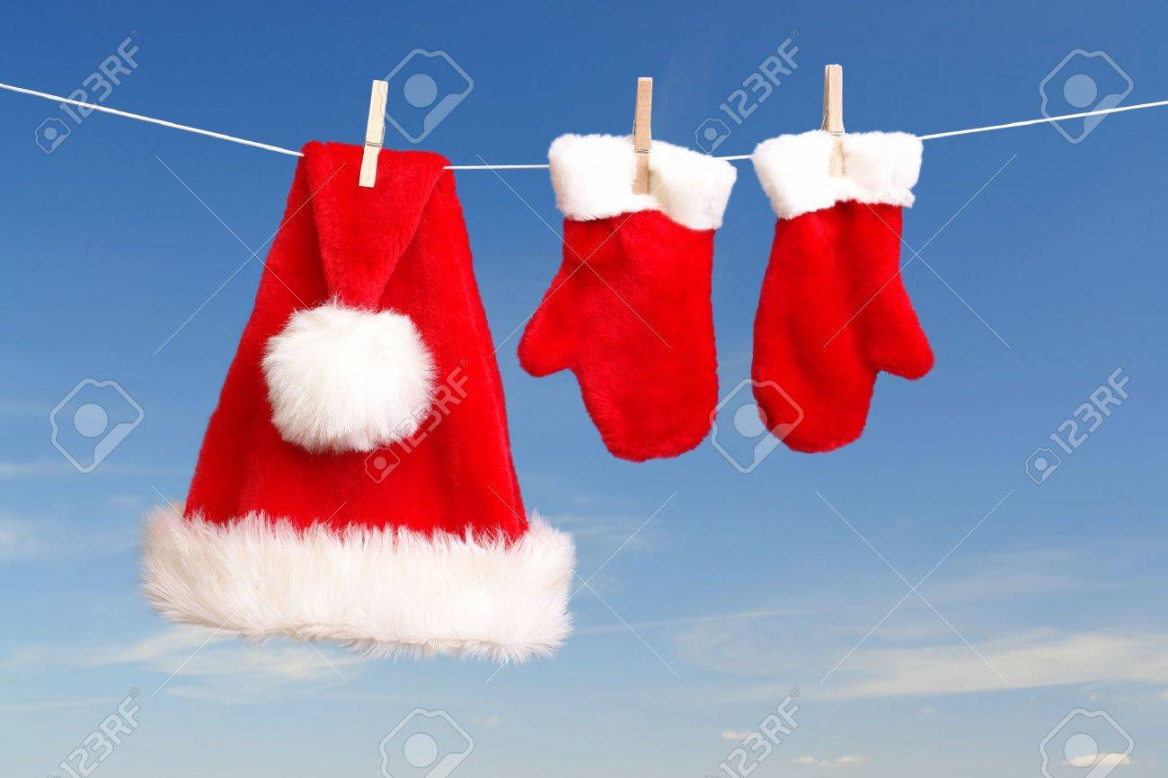 Red santa claus hat and pair of gloves drying in the open air hanging on clothes line affixed with wooden pegs Stock Photo - 2037502
