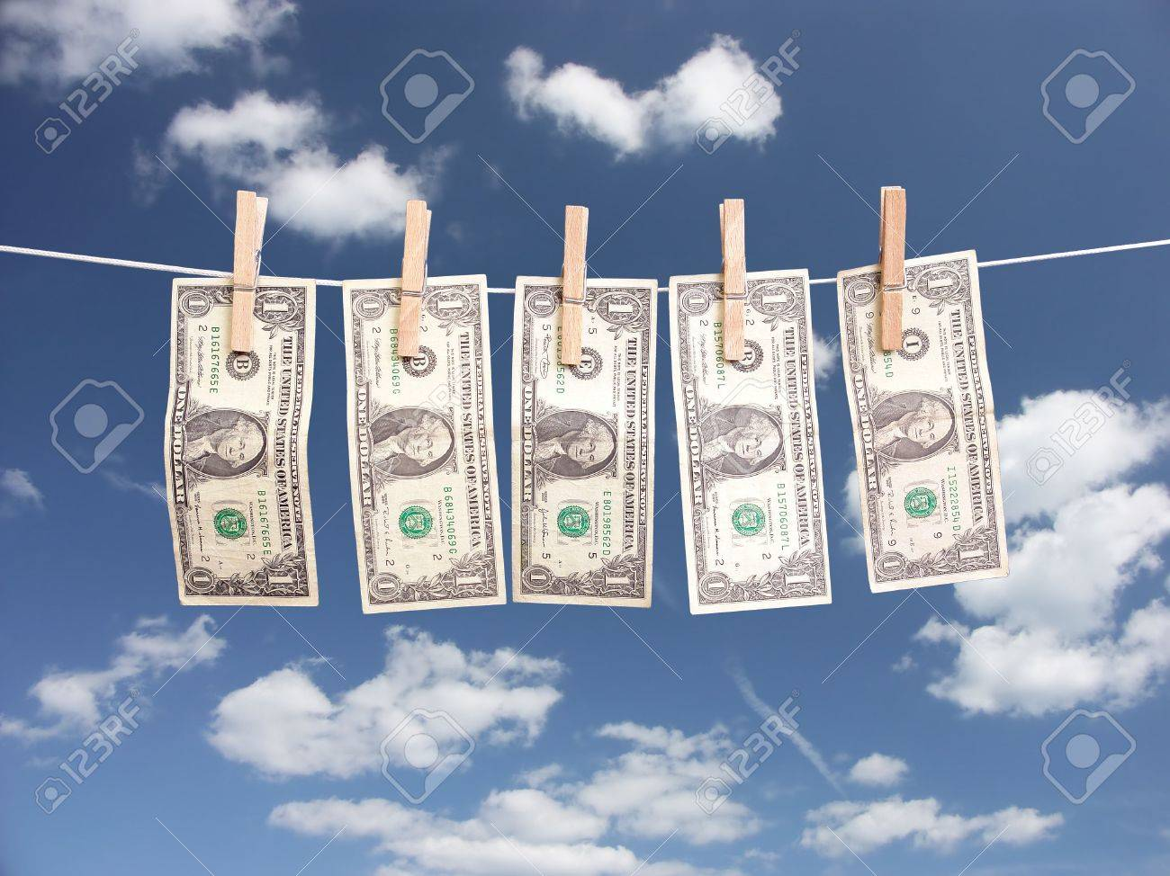 One Dollar Bills Hanging On Laundry Line Attached With Wooden Clips Over  Blue Sky Stock Photo
