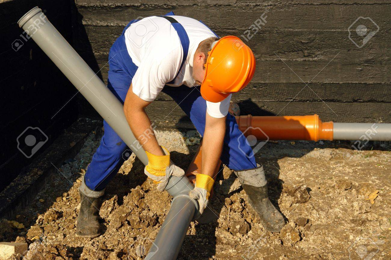 Plumber assembling pvc sewage pipes in house foundation Stock Photo - 4029527