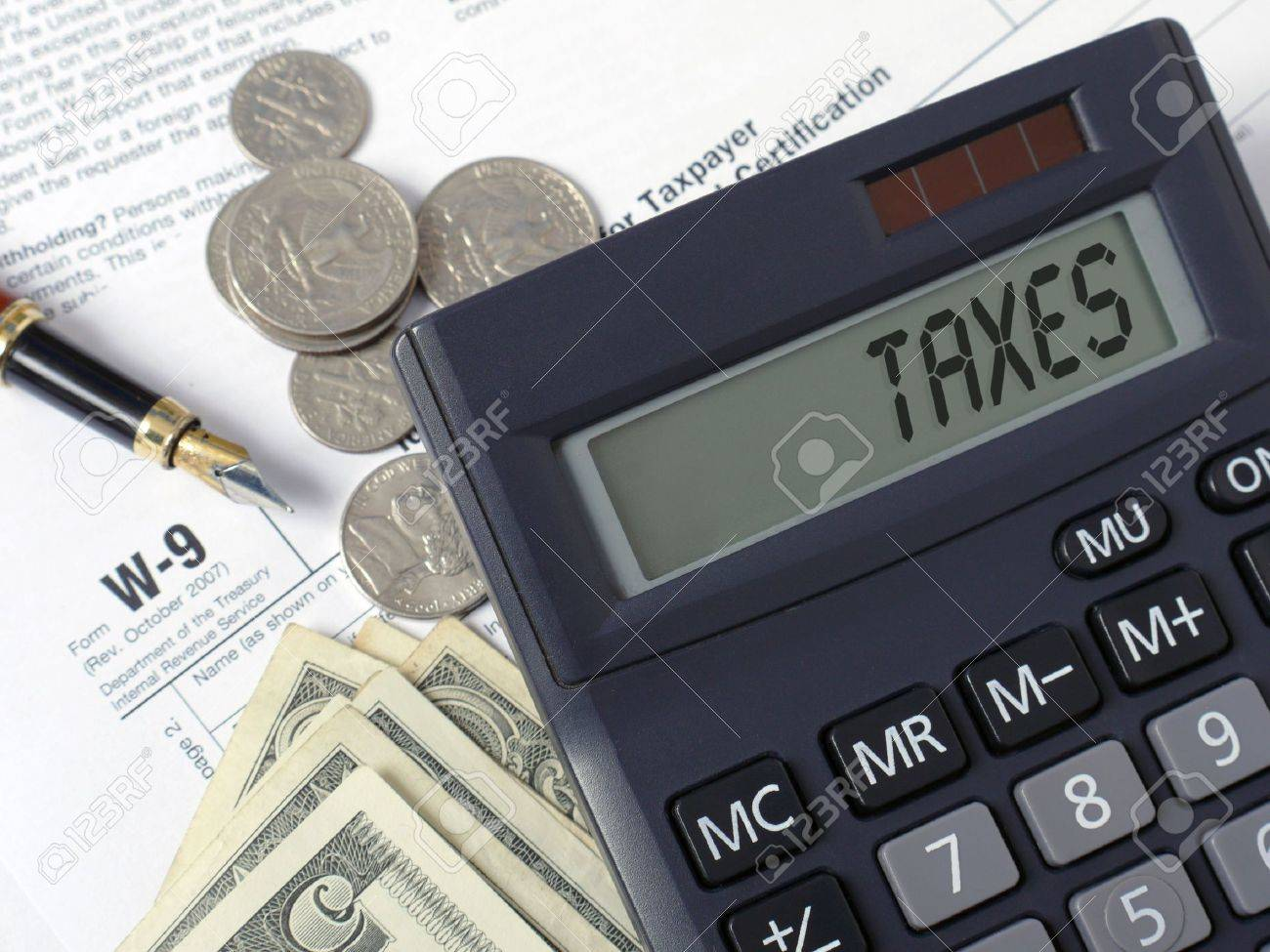 Calculator with lcd displaying Taxes word placed on W-9 income tax forms with pen, and american dollars Stock Photo - 4527475
