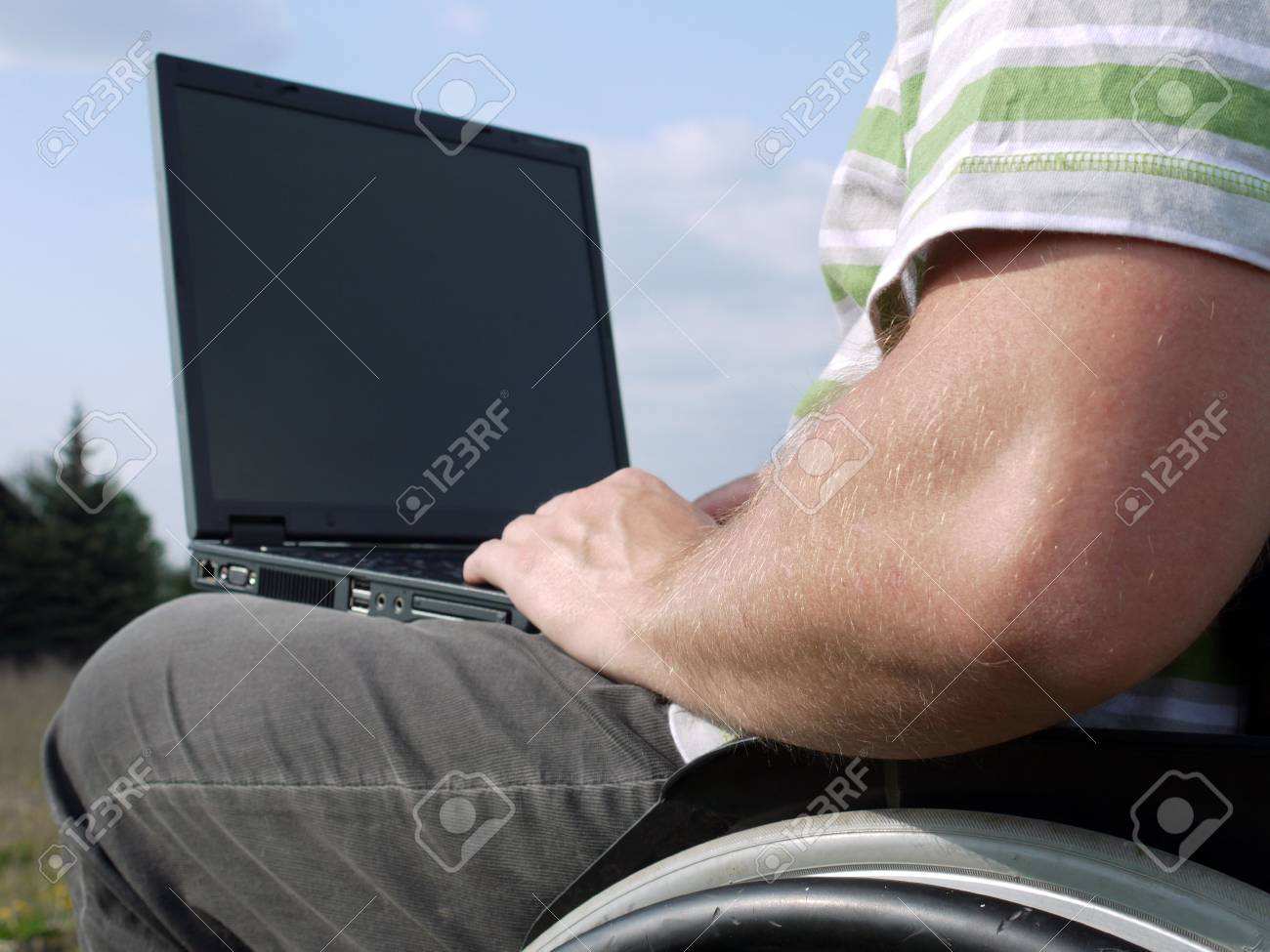 Handicapped man on wheelchair using laptop outdoors Stock Photo - 4802029