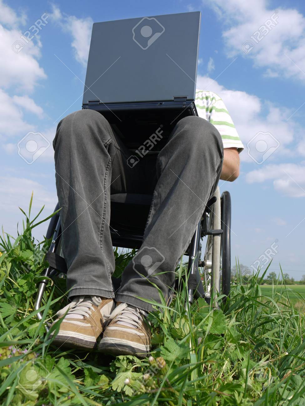 Handicapped man on wheelchair using laptop outdoors Stock Photo - 4802035
