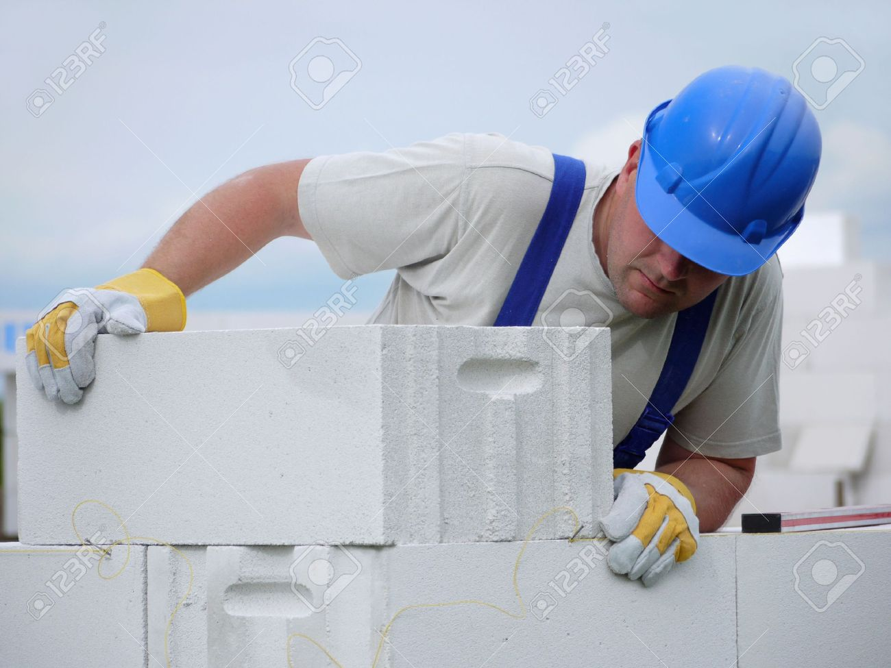Mason aligning aerated autoclaved concrete block of constructed house wall Stock Photo - 4988352