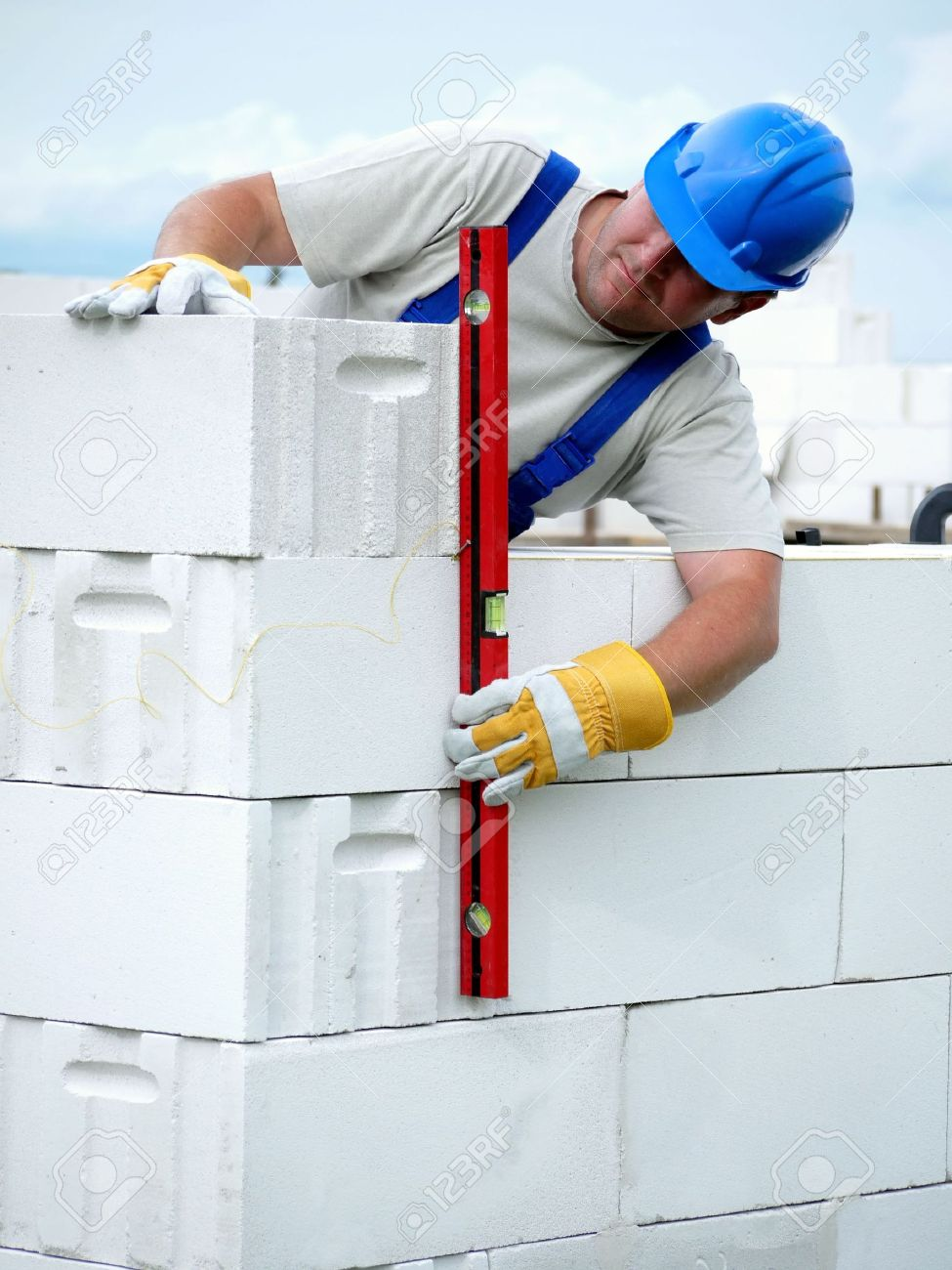 Mason checking plumb line of house wall being made from aerated autoclaved concrete blocks Stock Photo - 5014016