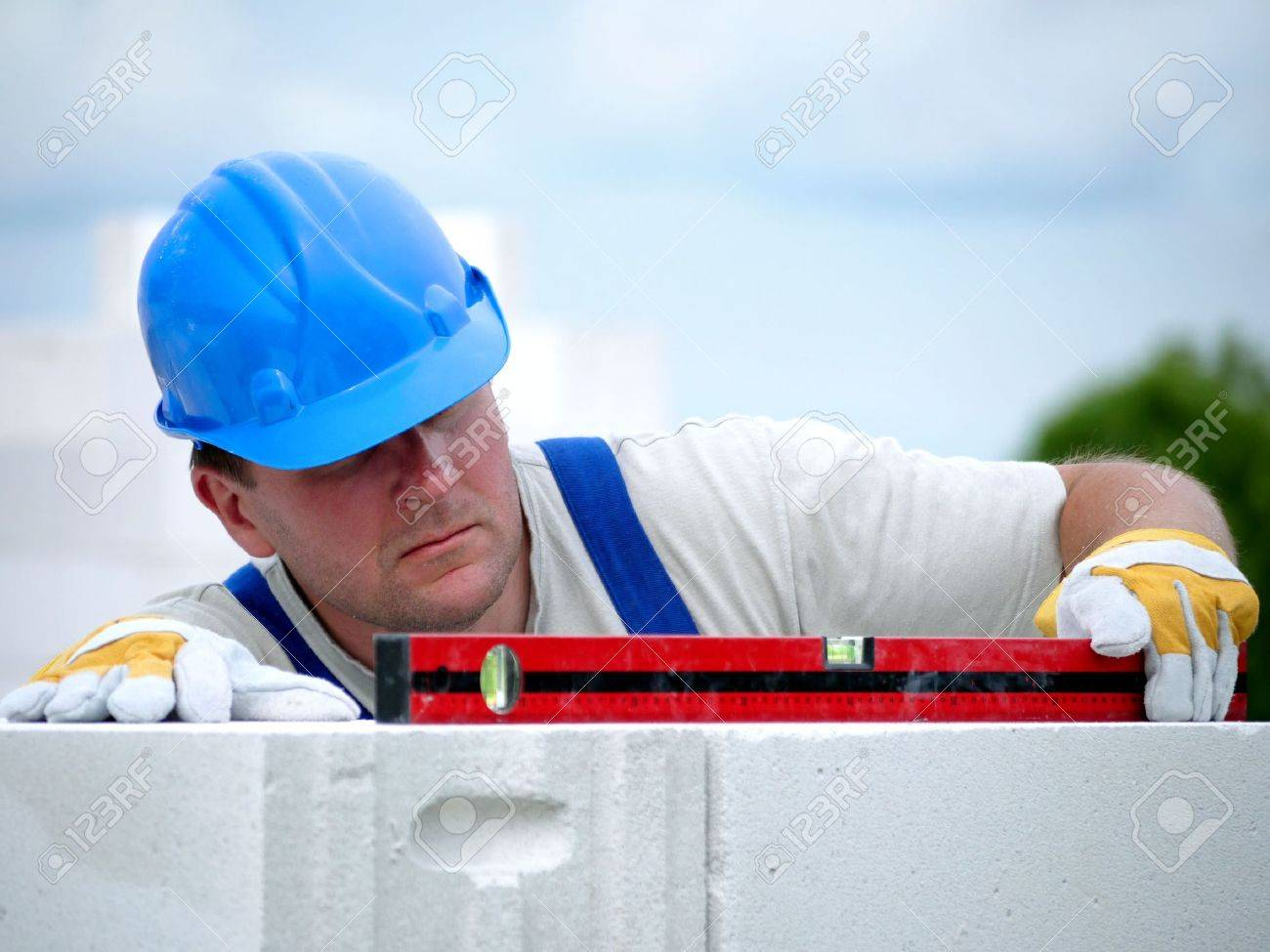 Mason checking horizontal level of house wall  layer being made from aerated autoclaved concrete blocks Stock Photo - 5026053