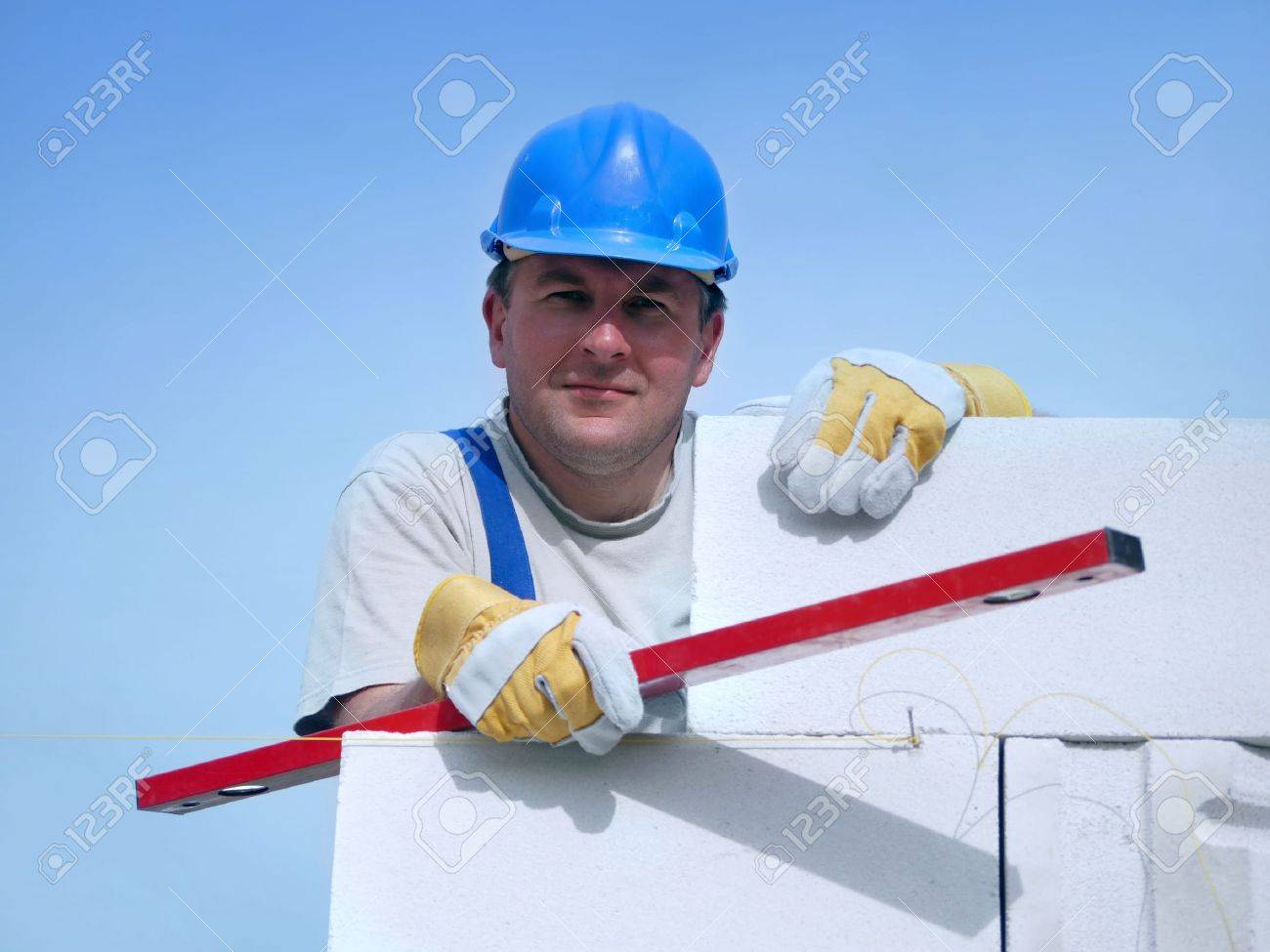 Mason wearing blue helmet posing resting on white block wall holding red level over blue sky Stock Photo - 5026055