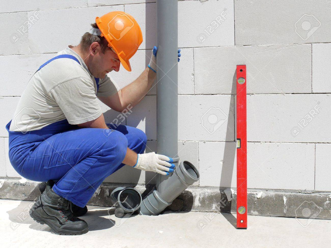 Plumber assembling pvc sewage pipes inside unfinished house Stock Photo - 5034704