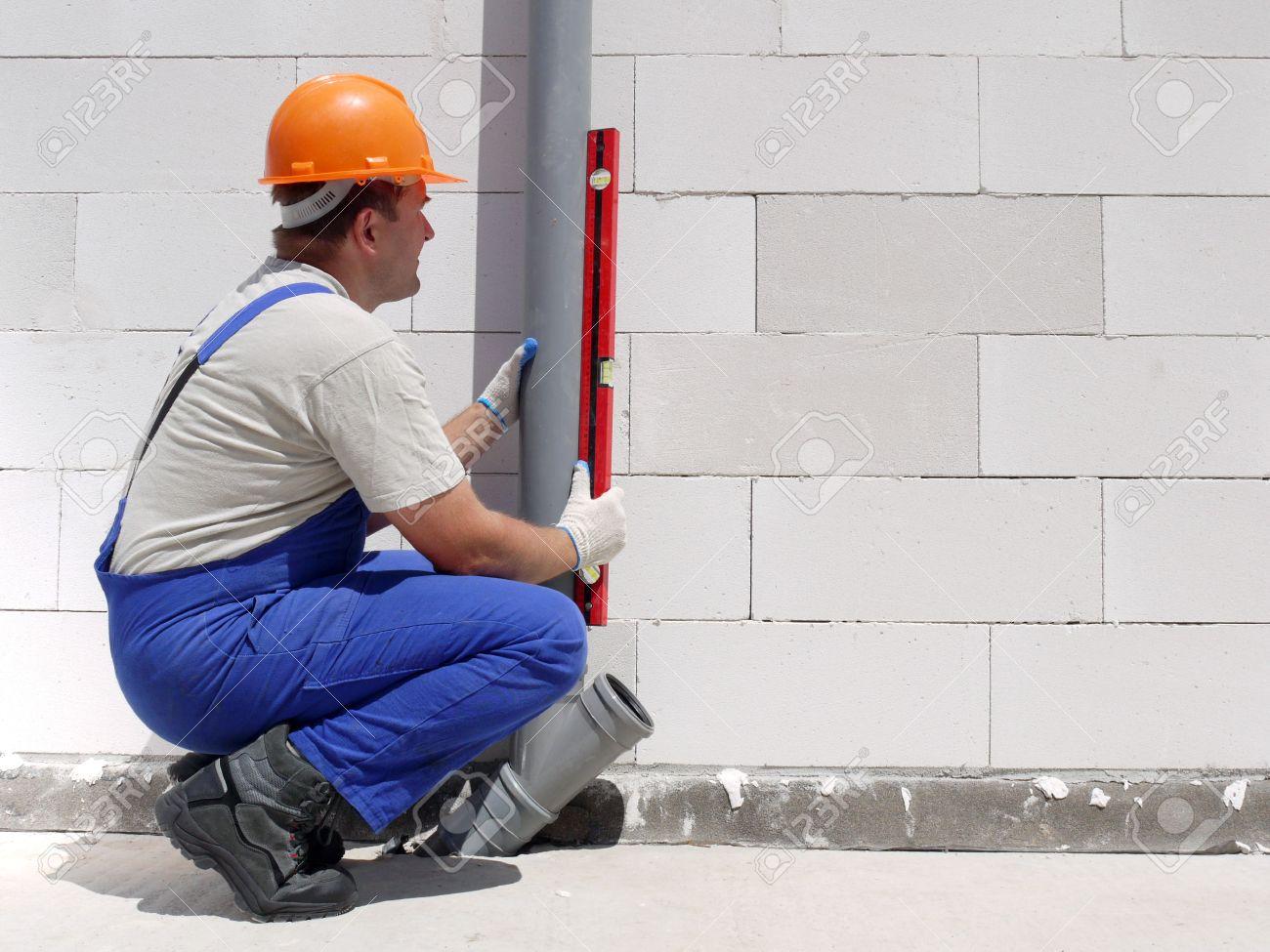 Plumber Using Level For Checking Plumb Line Of Assembled Pvc Stock
