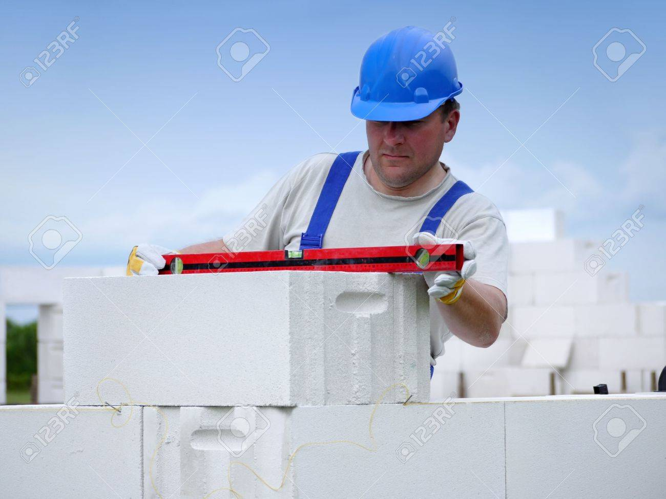 Mason checking horizontal level of house wall  layer being made from aerated autoclaved concrete blocks Stock Photo - 5059332