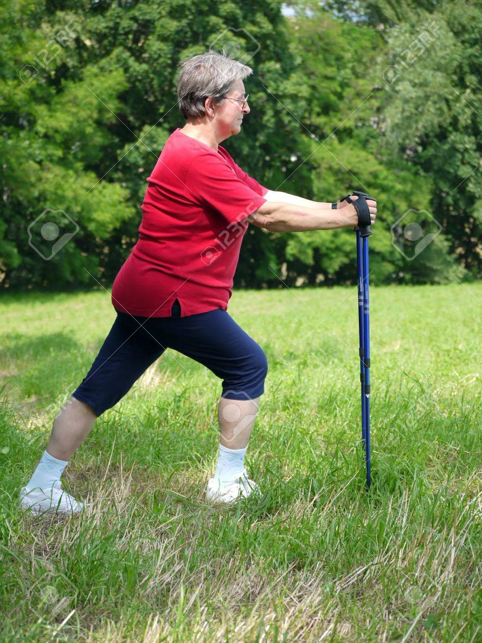 Senior woman doing a series of warm-up exercises with walking poles Stock Photo - 5174696