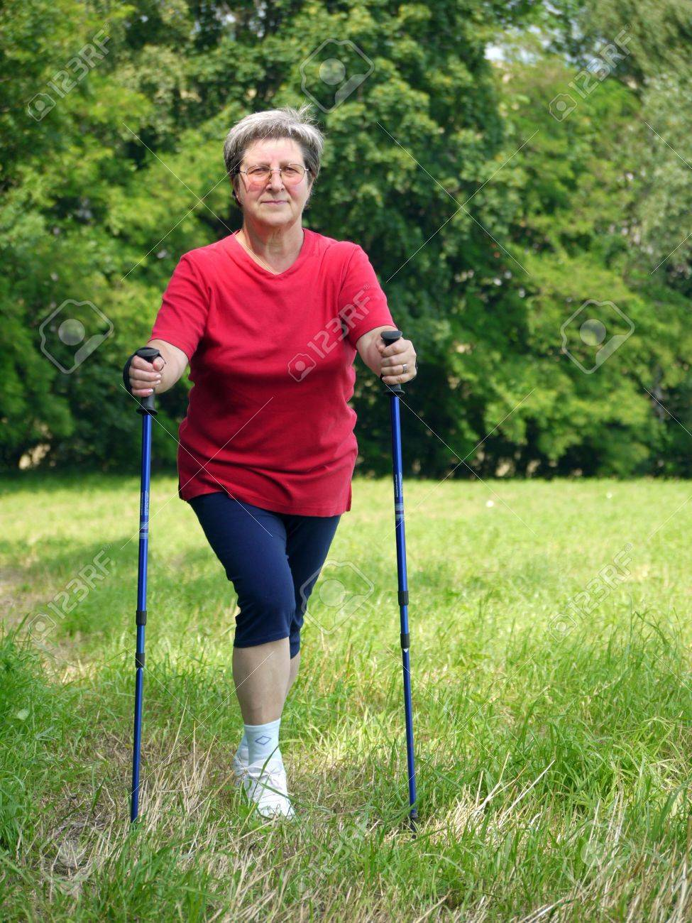 Senior woman doing a series of warm-up exercises with walking poles Stock Photo - 5174697