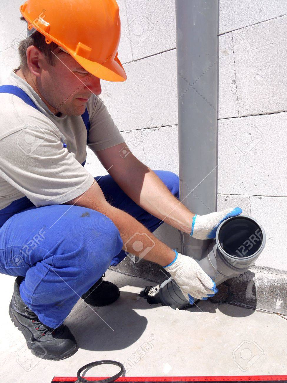 Plumber assembling pvc sewage pipes inside newly built house Stock Photo - 5190177