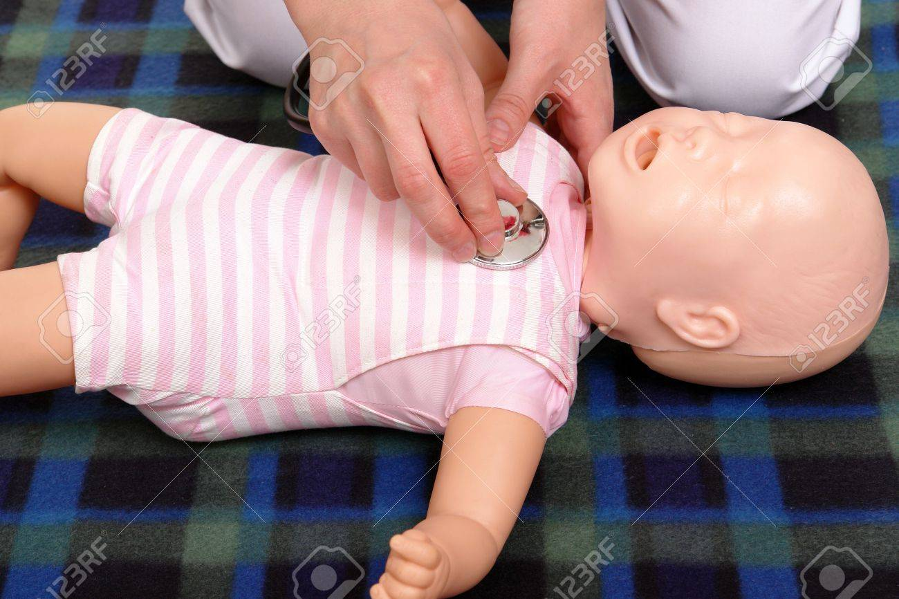 First aid instructor using infant dummy to demonstrate how to examine baby with stethoscope Stock Photo - 5280034