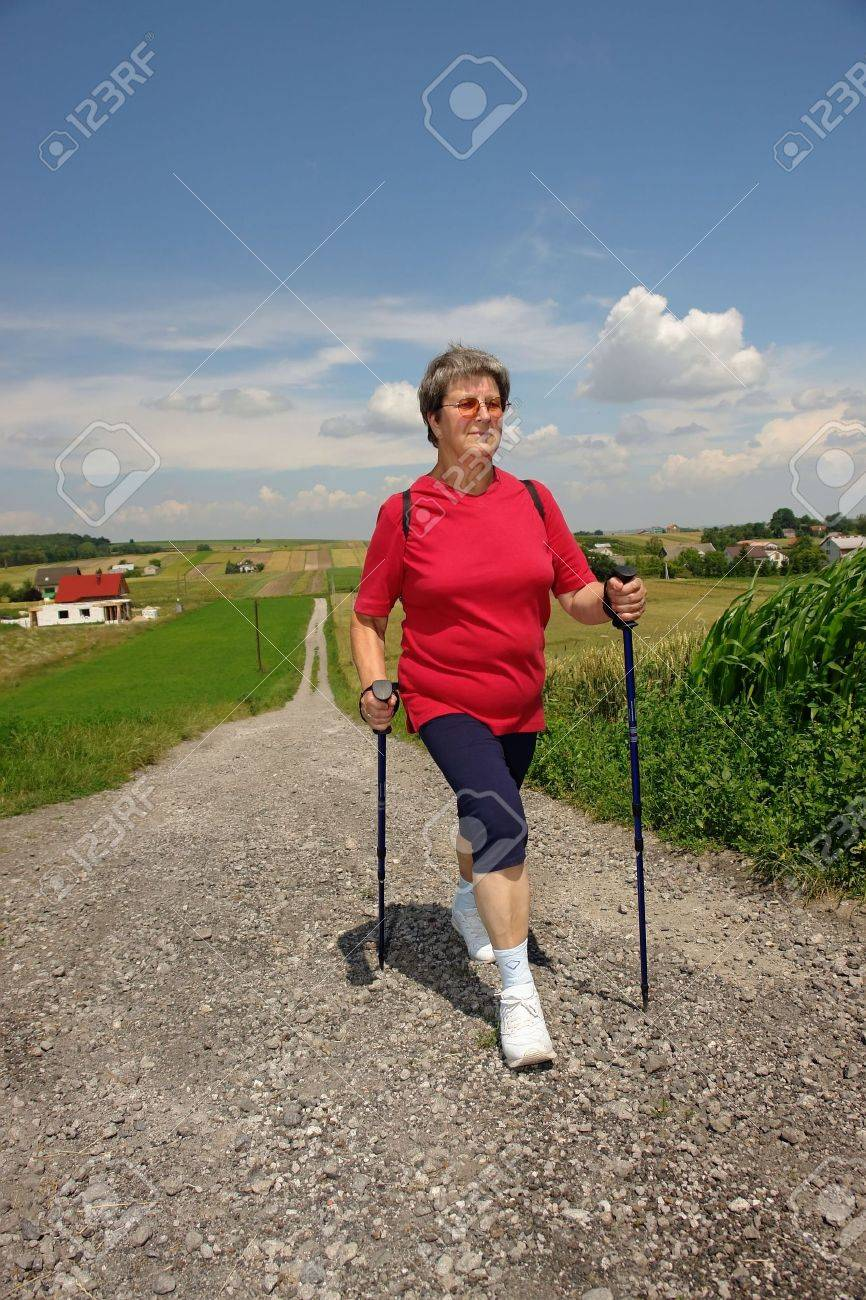 Senior woman doing nordic walking in the countryside Stock Photo - 5280035