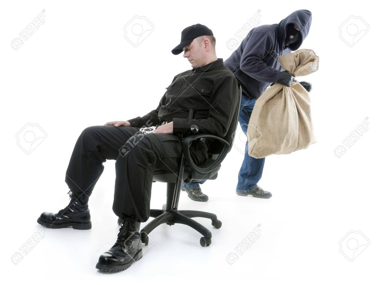 Security man sleeping on armchair being unaware of masked burglar stealing behind his back Stock Photo - 25987932