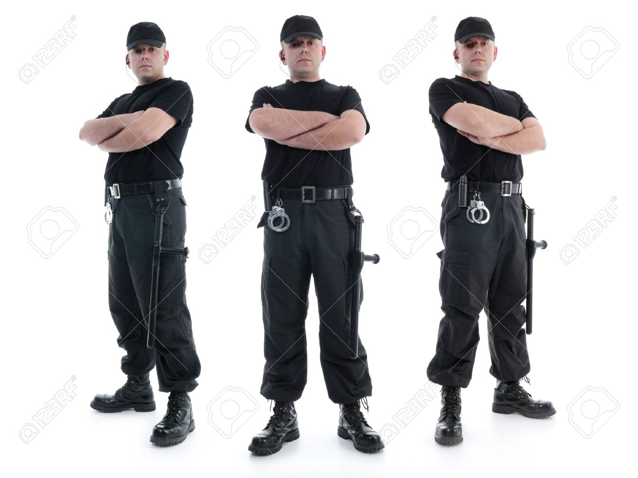 Three security men wearing black uniform equipped with police clubs and handcuffs standing confidently with arms crossed from left to right, shot on white Stock Photo - 25987954