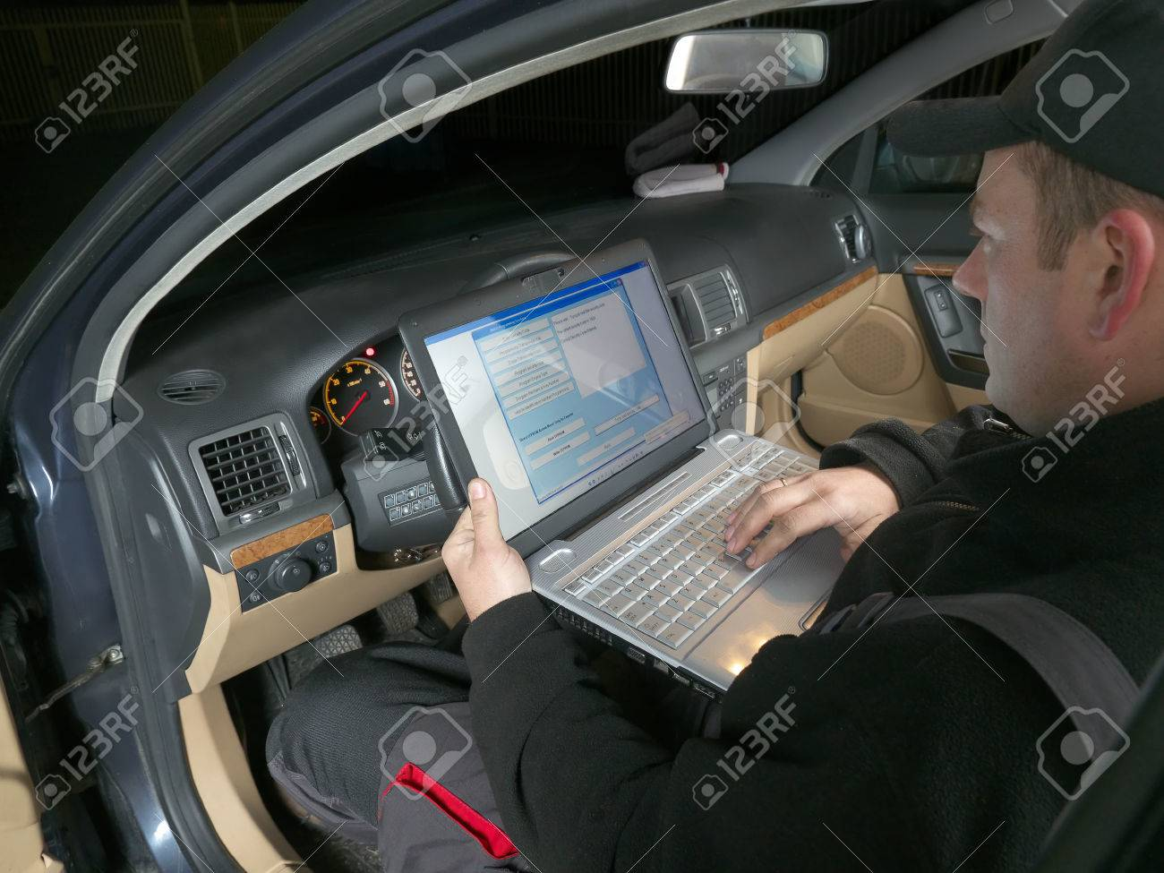 Auto mechanic checking vehicle identification number of the car using laptop hooked up to the car onboard computer Stock Photo - 26349870