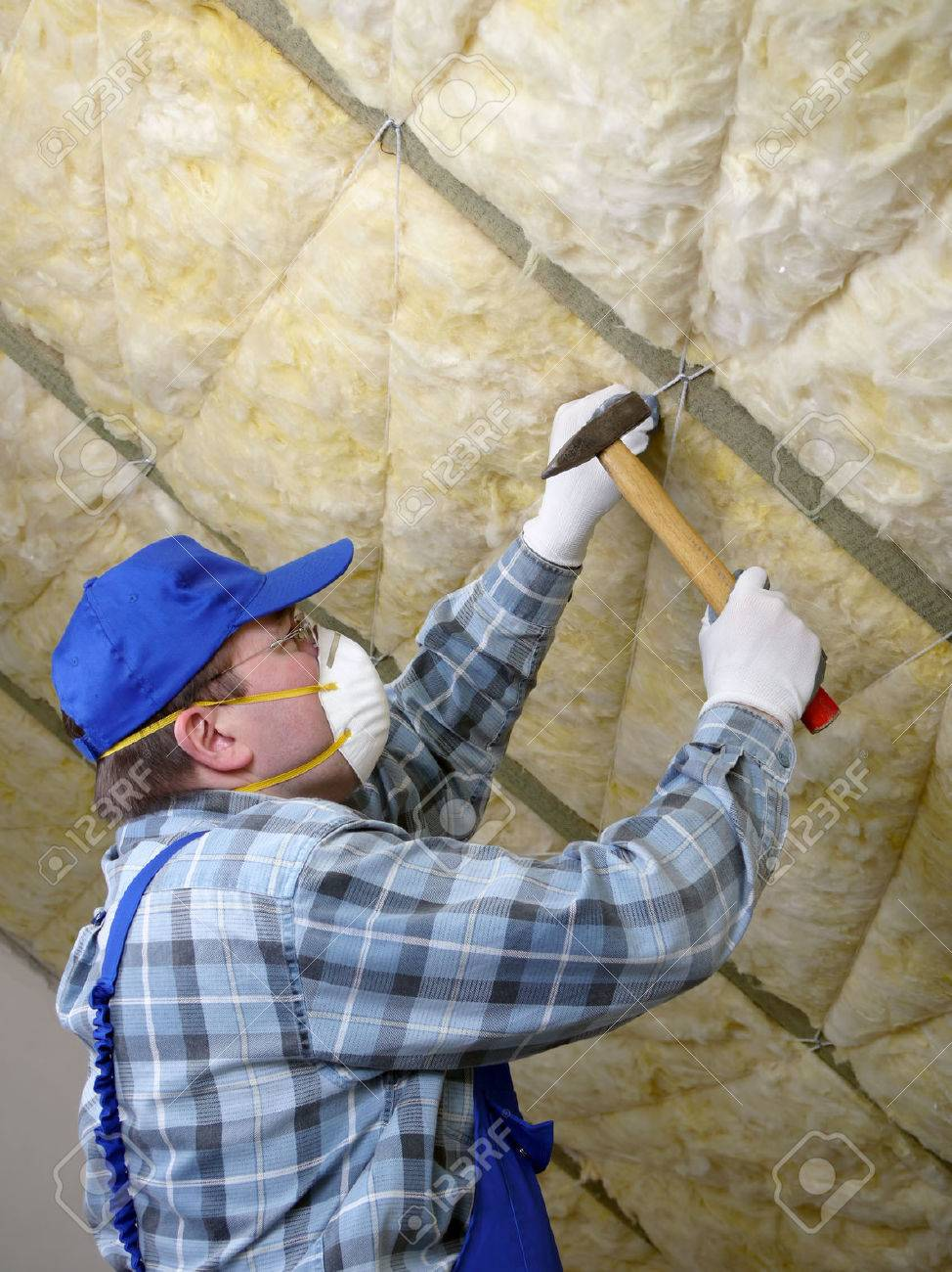 Worker thermally insulating a house attic using mineral wool Stock Photo - 26542836
