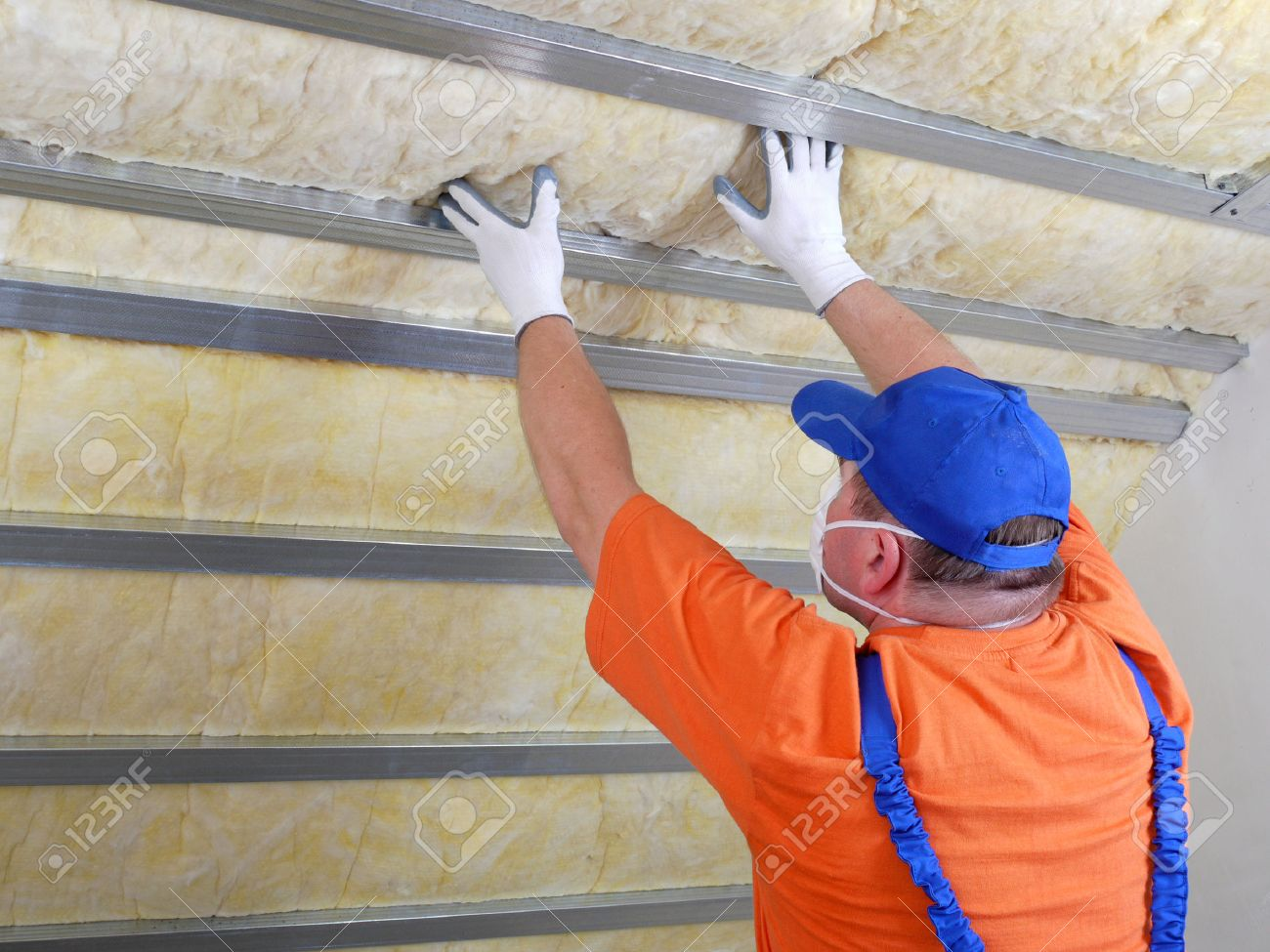 Construction worker thermally insulating house attic with mineral wool Stock Photo - 26775486