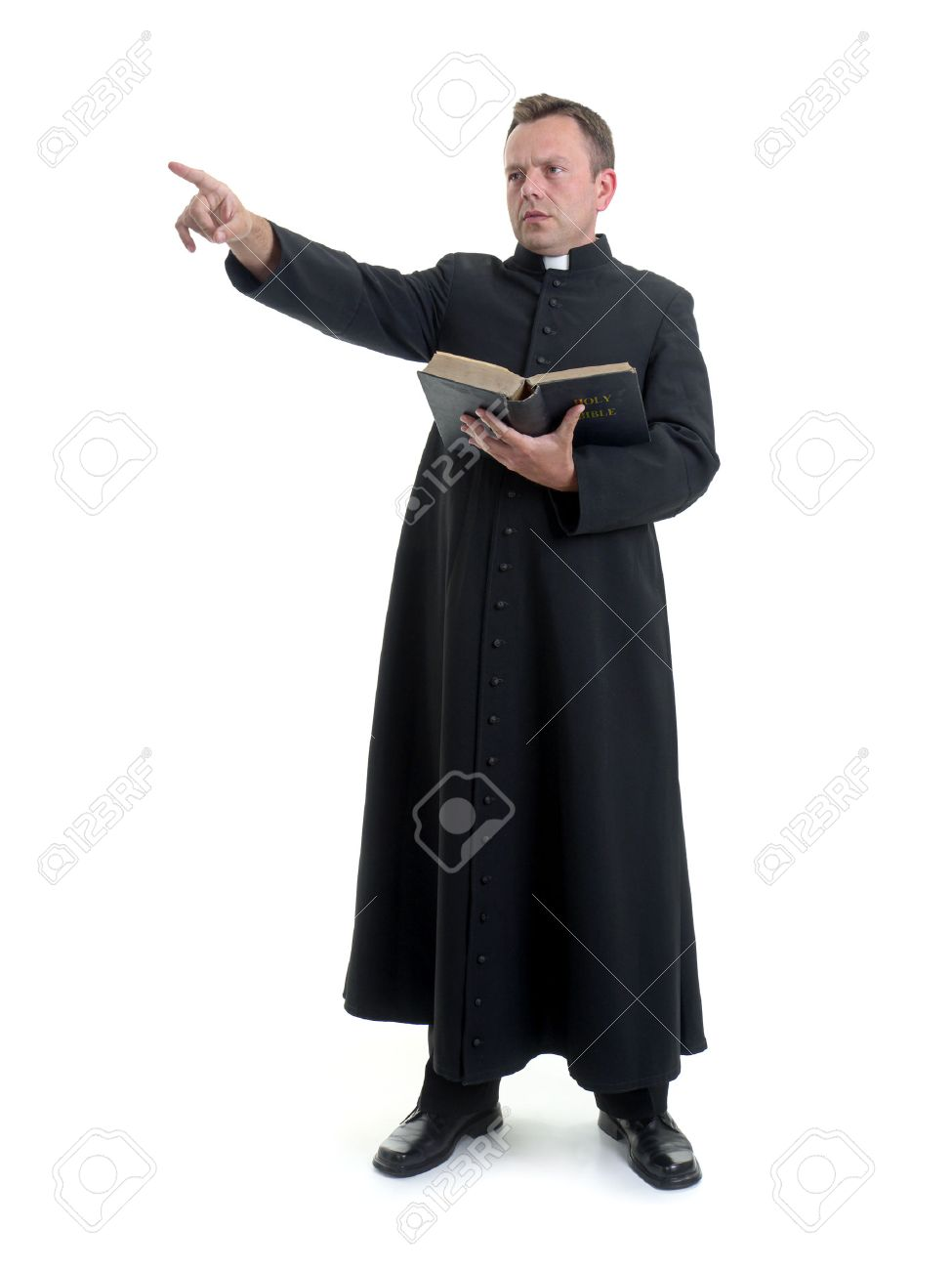 Catholic priest preaching holding open the Bible book shot on white Stock Photo - 27516952