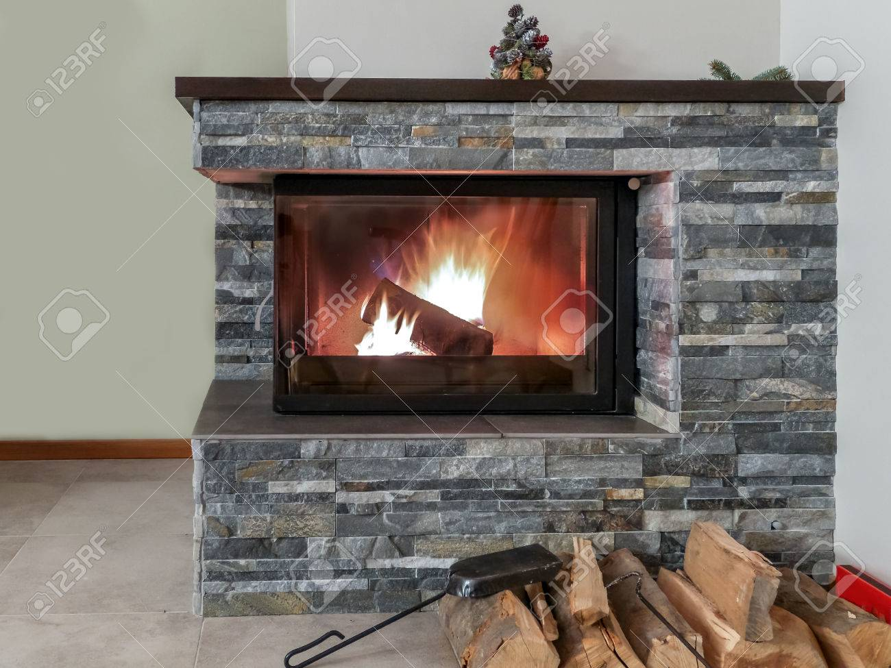 chimenea de piedra con lea encendida foto de archivo
