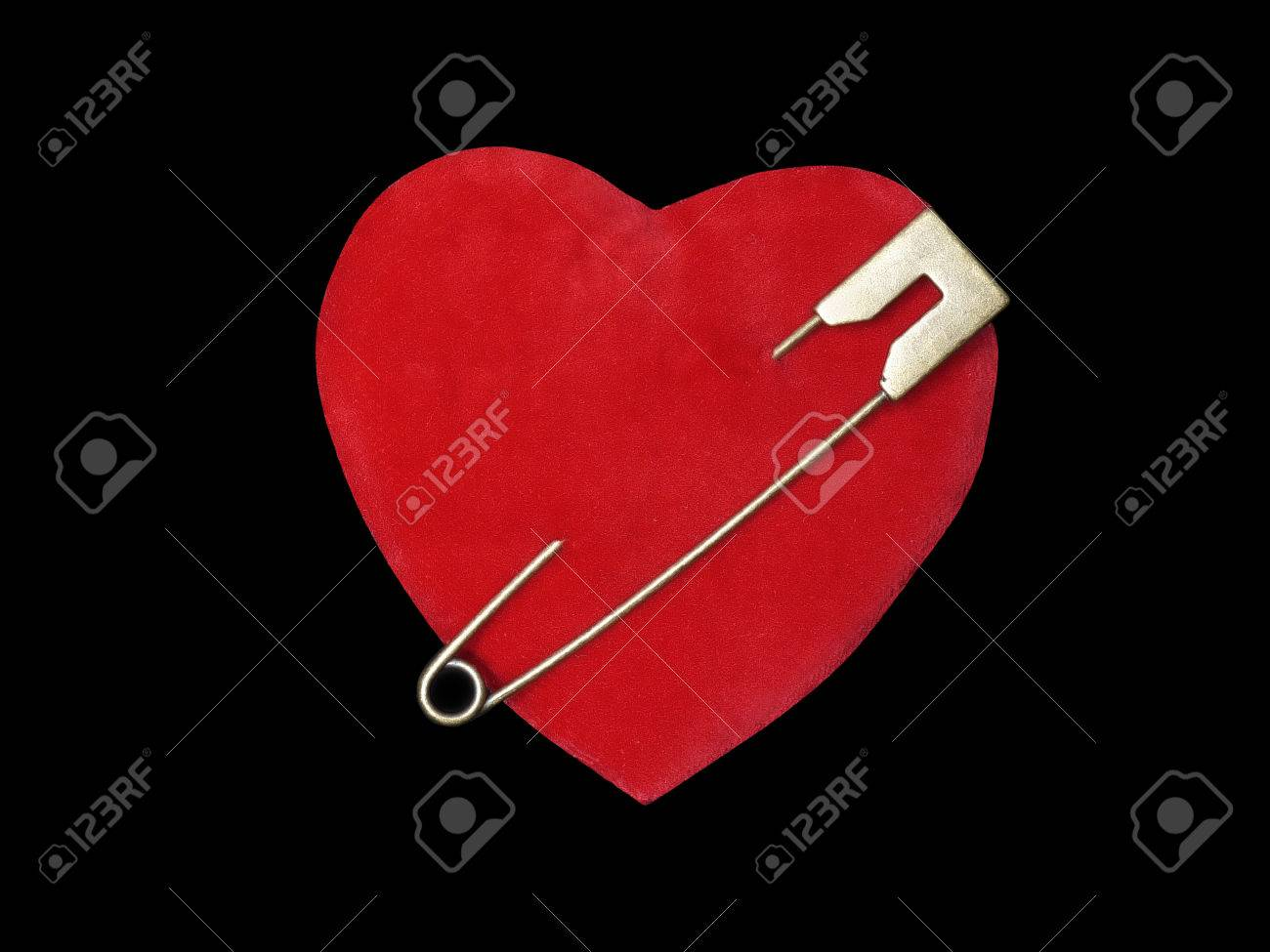 99bf0e096dcba Red suede heart pierced with golden safety pin over black background