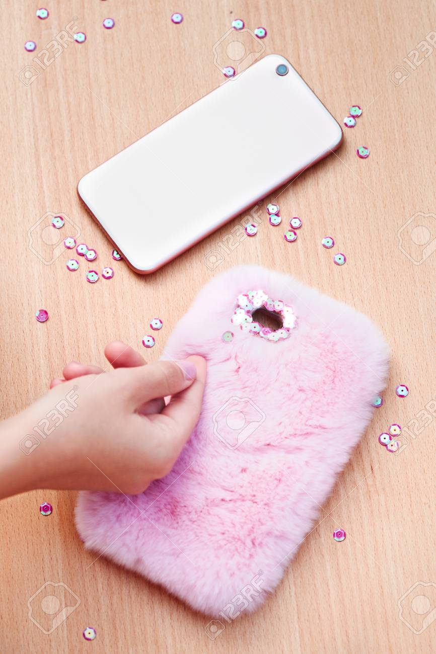 Close Shot Of Female Hand Decorating Phone Case With Sequins Stock