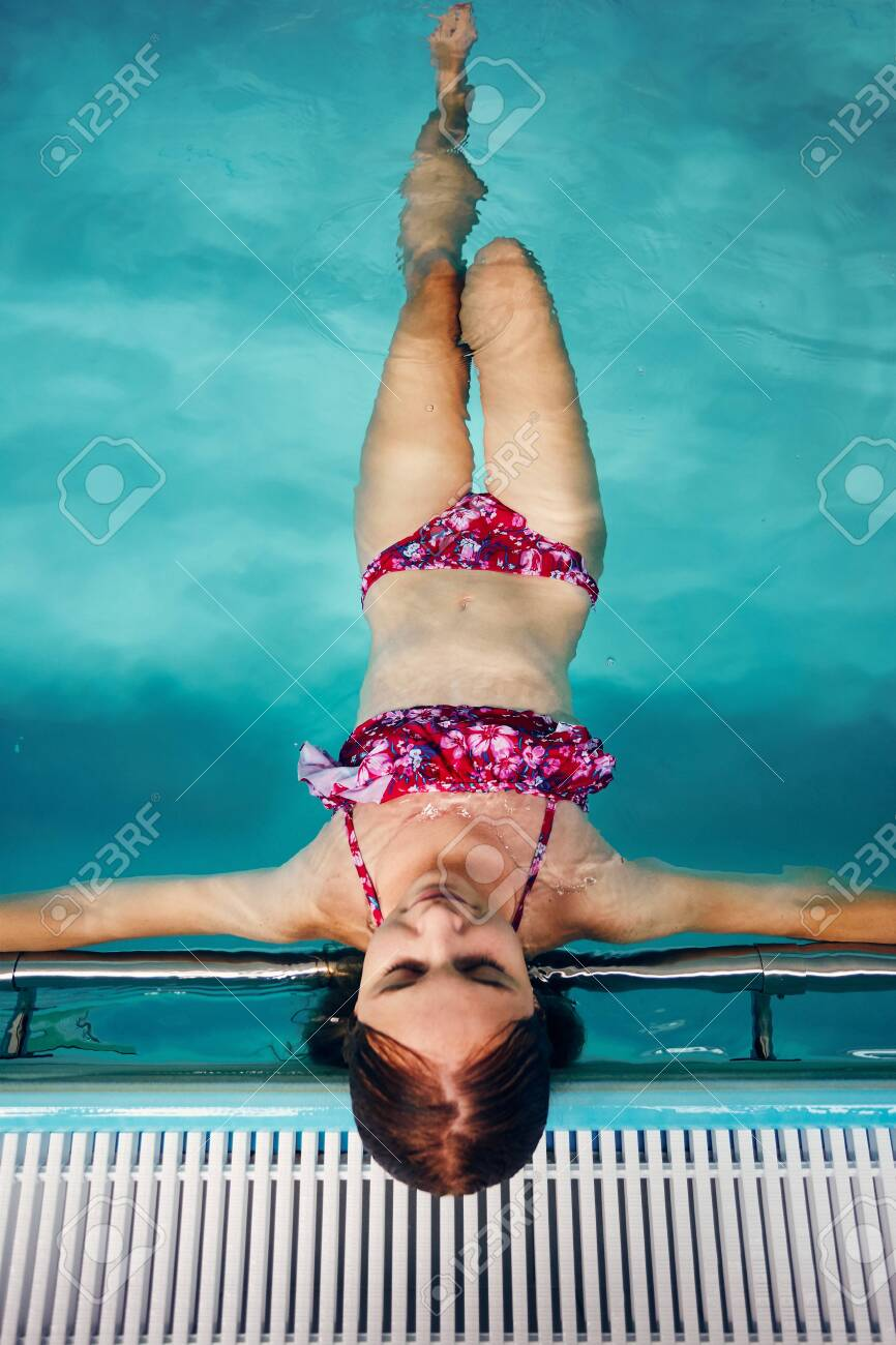 Young woman swimming and relaxing in swimming pool. Candid people, real moments, authentic situations - 128705548