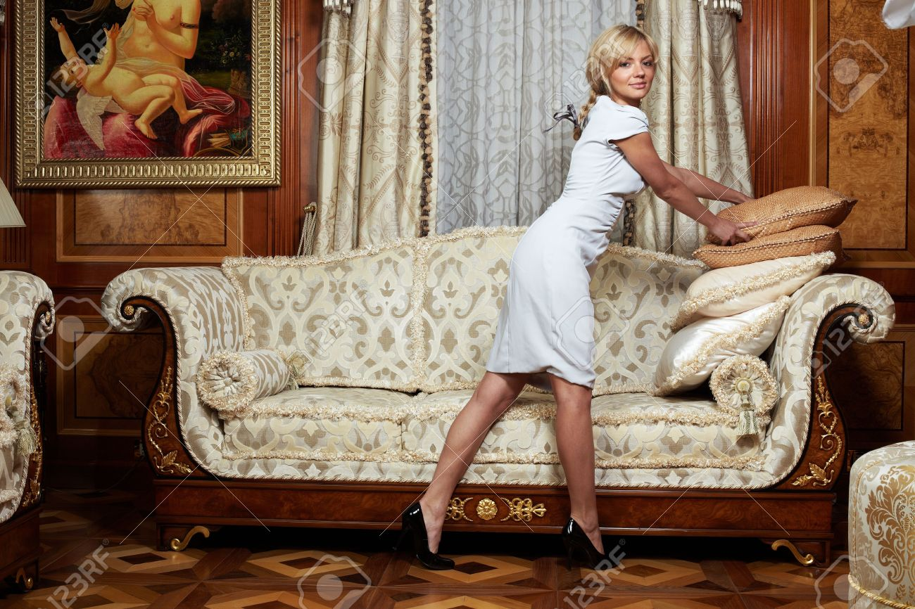 Attractive maid making a sofa in luxury hotel Stock Photo - 4794480
