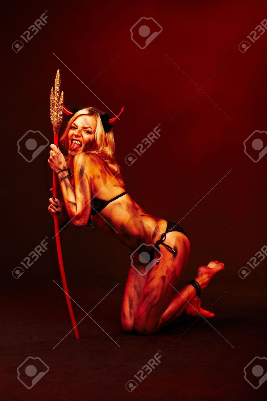 Beautiful vimpire devil with trident and Halloween accessories on deep red black Stock Photo - 5745926