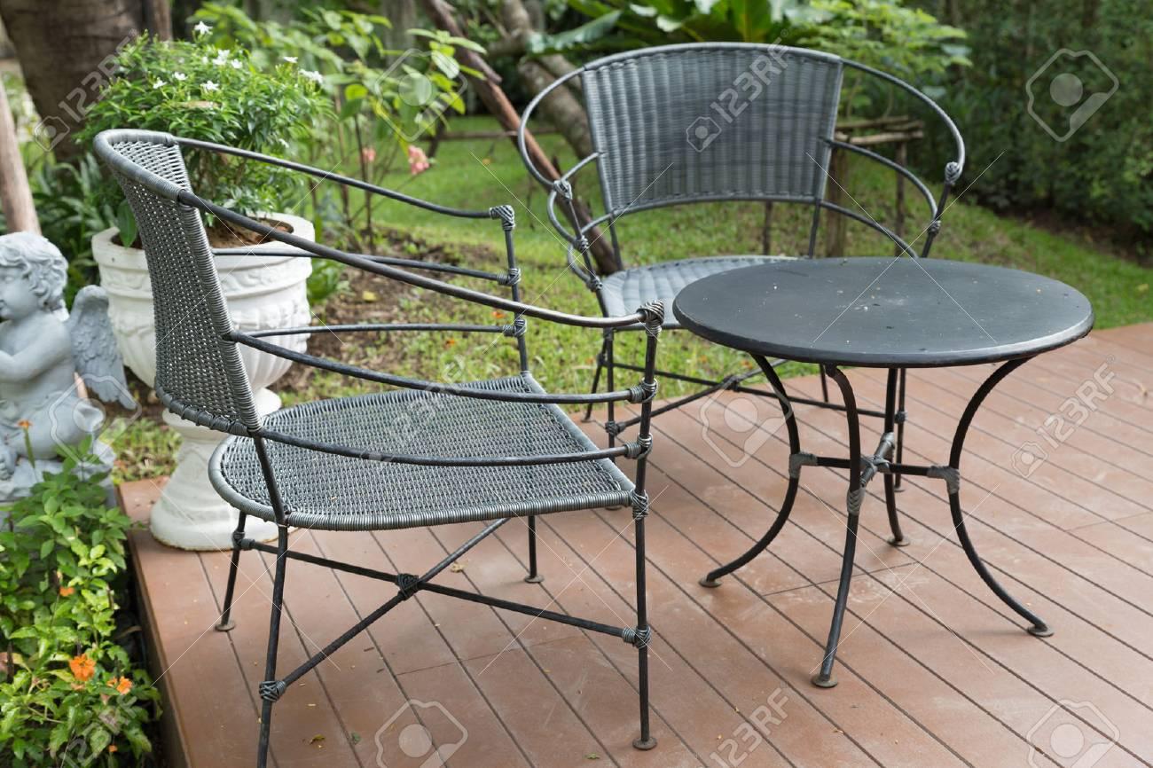 Chaise en osier rotin et un bureau sur le patio côté jardin jour
