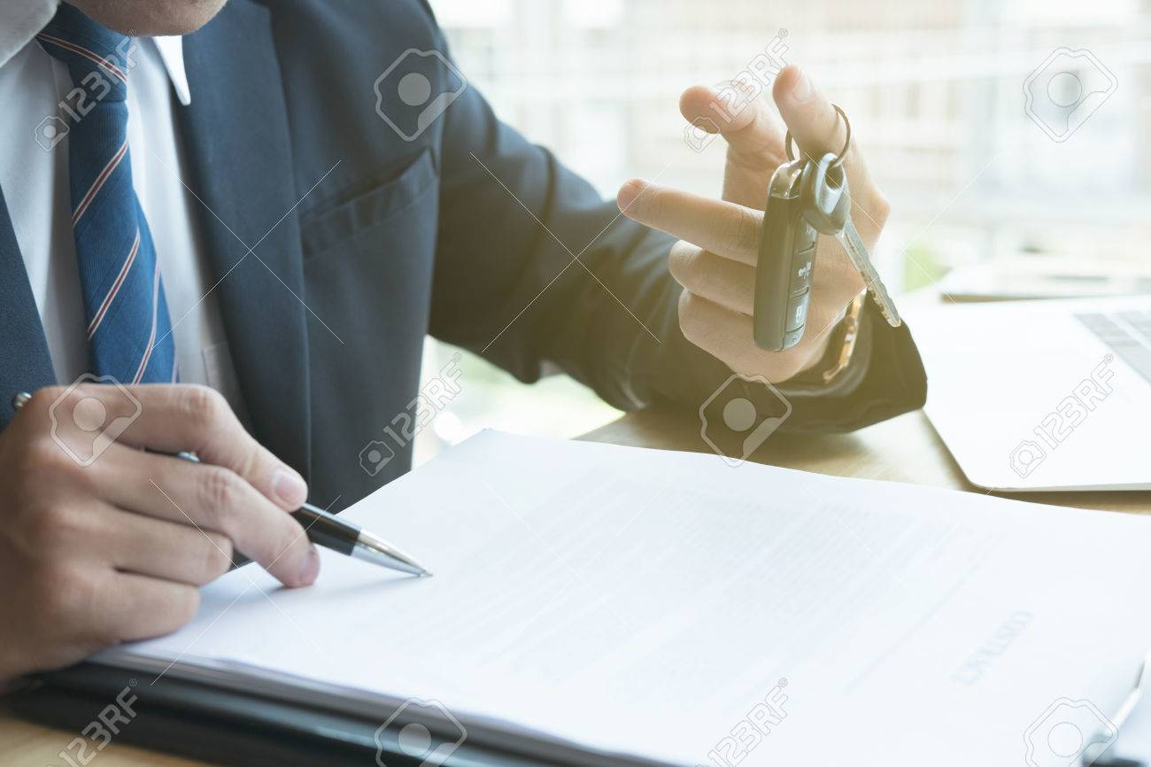 young businessman sign sales contract with car key at office