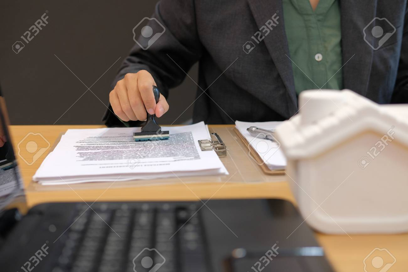 real estate agent using stamper for stamping approved on mortgage
