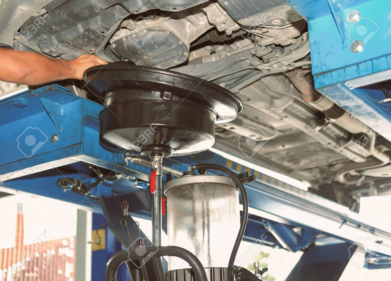 vehicle lift up by hydraulic for motor oil change and transmission inspection. changing engine oil in automobile repair service. maintenance and checkup in car workshop. - 134550242