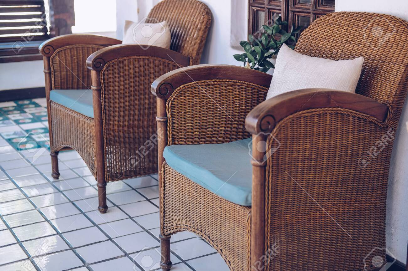 photo old vintage retro wicker rattan armchair chair on terrace balcony living room interior