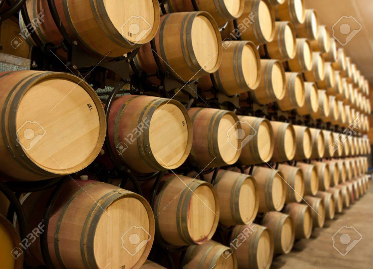 oak wine barrels. oak wine barrels stacked up in a winery aging room stock photo 7415780 t