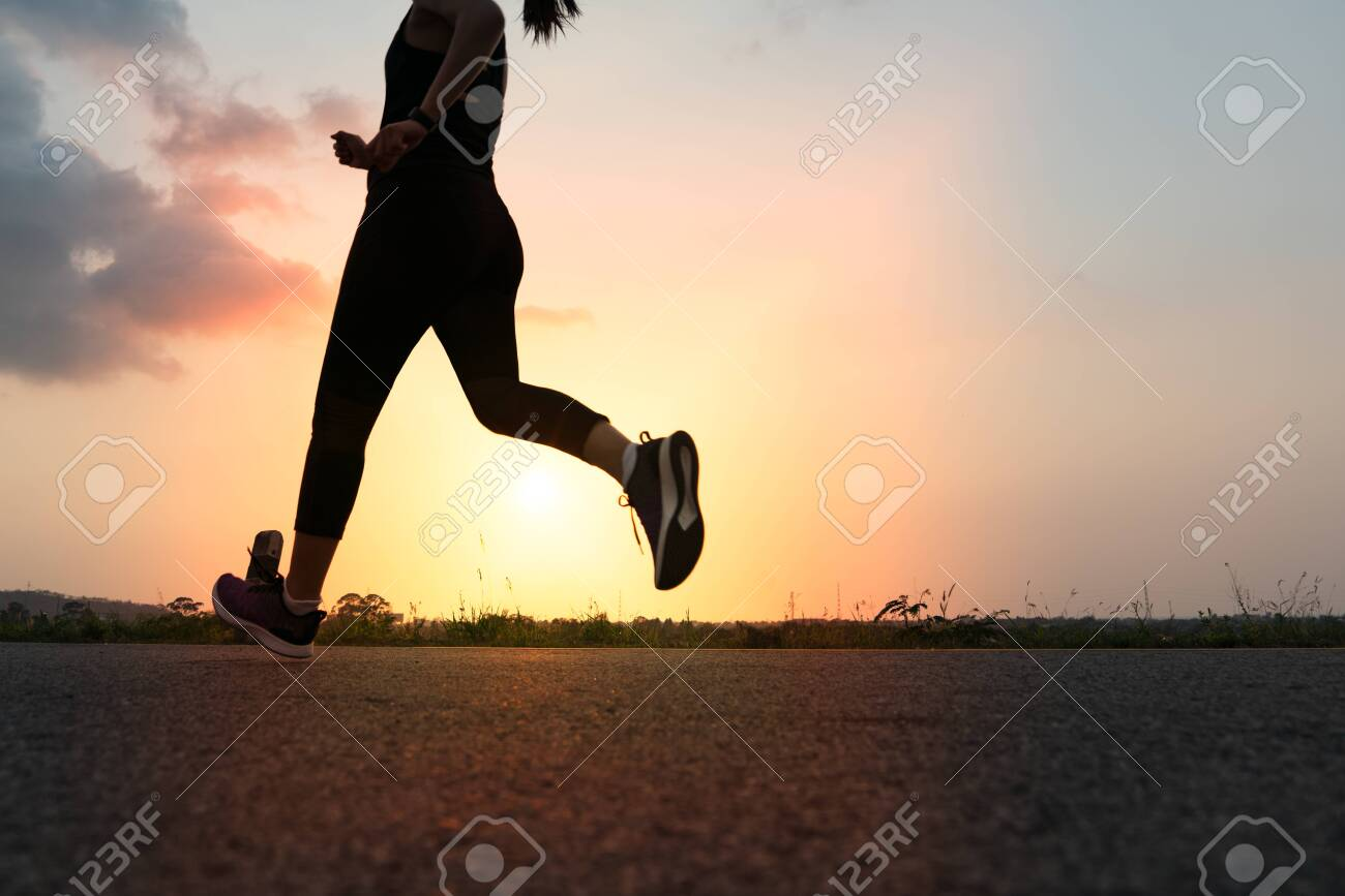 sport woman running on a road. Fitness woman training at sunset - 128287176