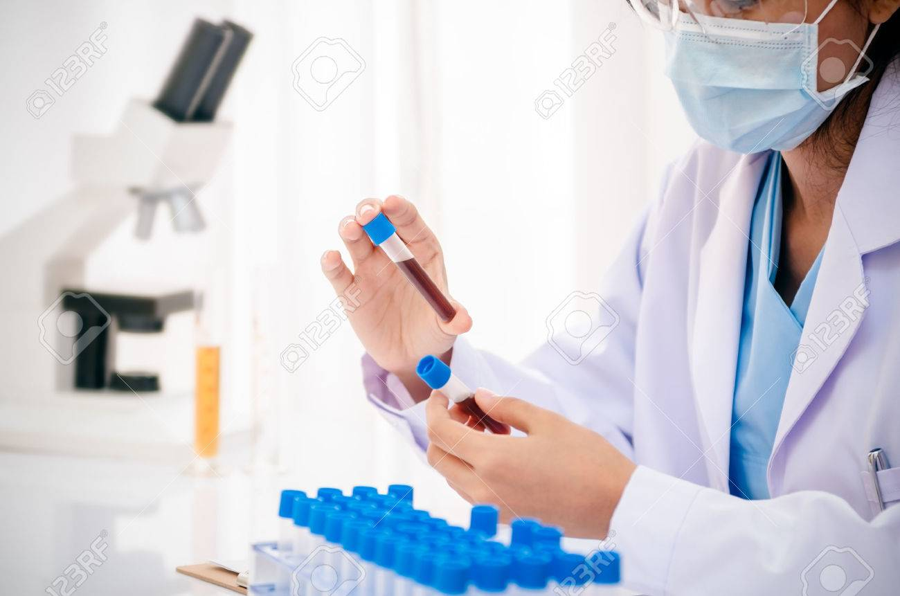 close up of scientist holding and examining blood sample in lab - 41452362