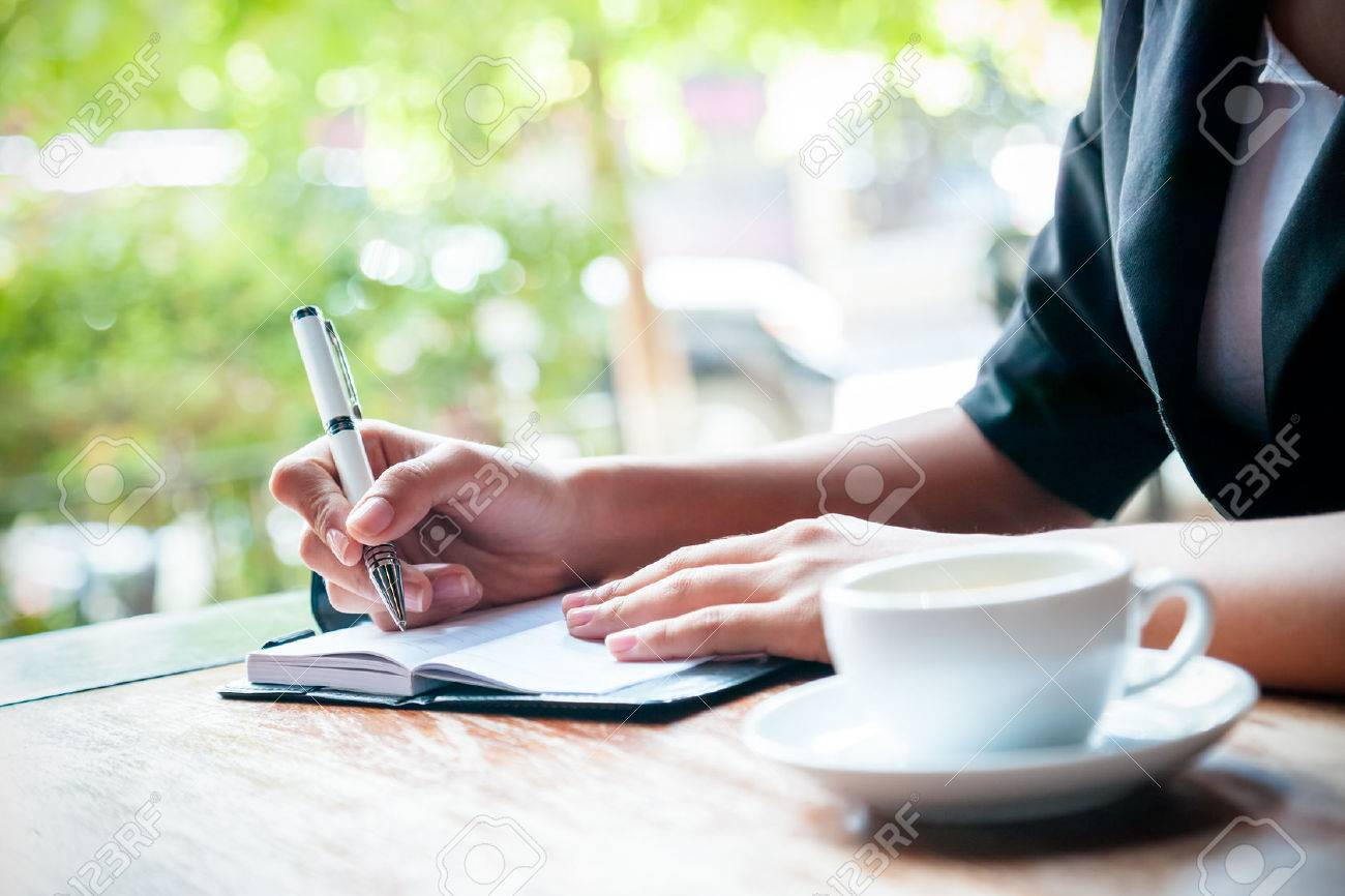 close up of woman writing journal and cup of coffee stock photo