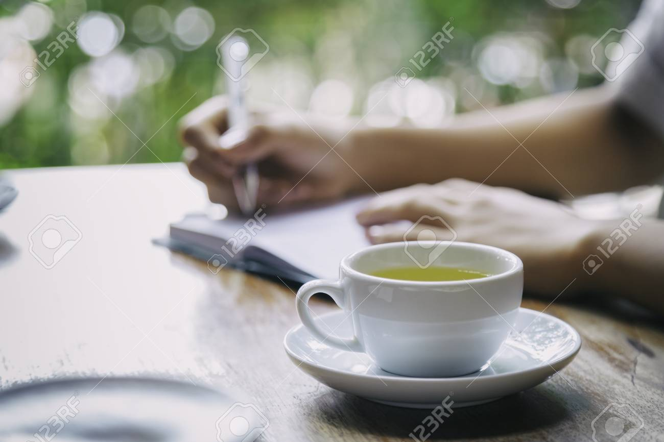 cup of tea with background of woman writing - 43281104