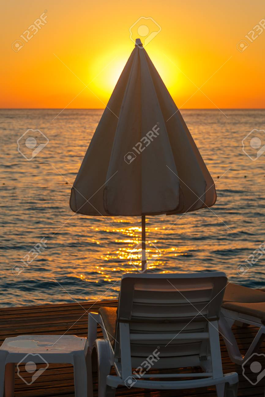 Chaise Lounge And Sunshade Umbrella In Light Of Sunset Stock Photo