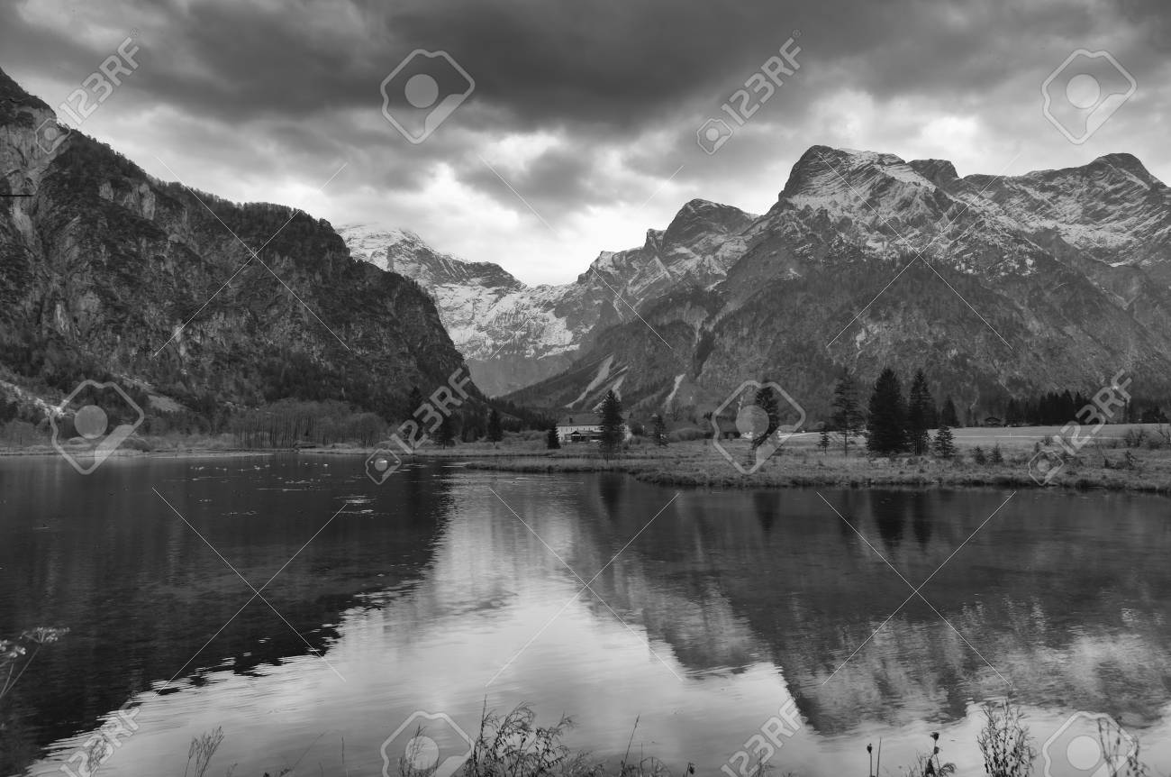 Black and white photo of the alpine lake surrounded with mountains stock photo