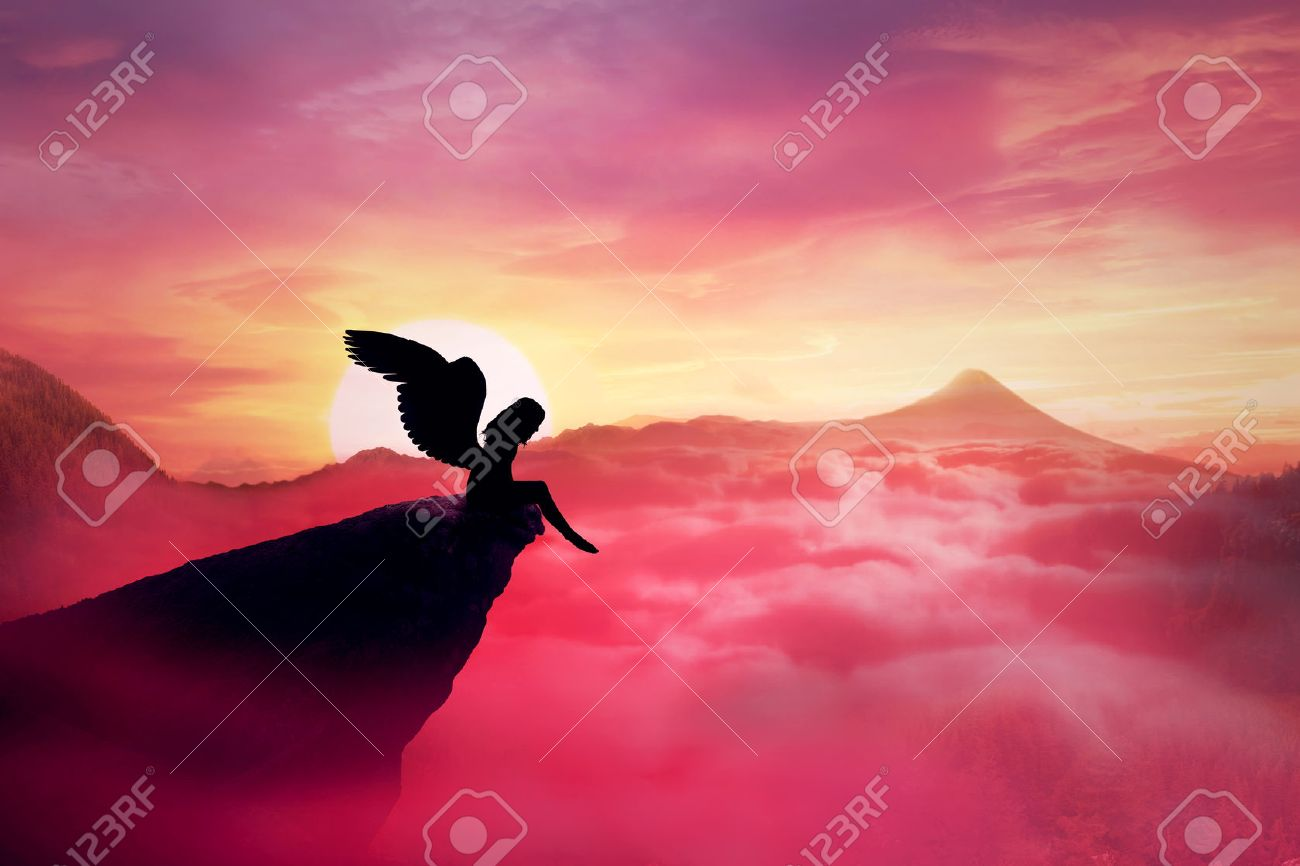 Silhouette of a lonely fallen angel with long wings standing on a cliff against a paradise sunset. Dusk sky over the clouds in the mountains. Heaven landscape scene screen saver - 54628035
