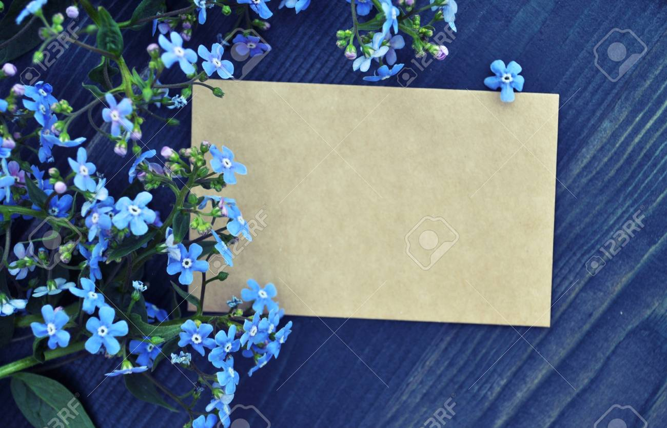 Empty paper list and bouquet of forget me not blue flowers on empty paper list and bouquet of forget me not blue flowers on wood background izmirmasajfo