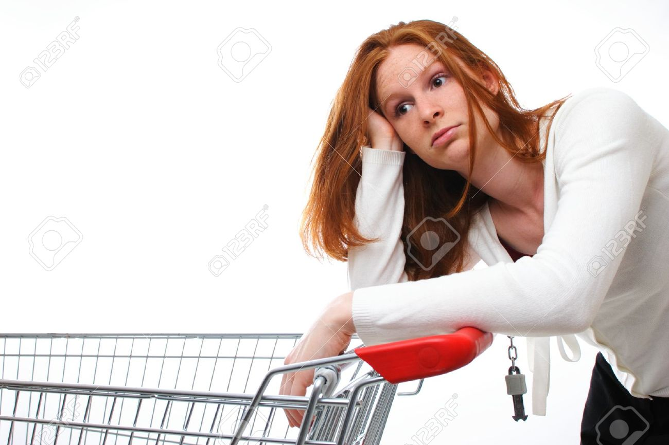 A sad shopping girl leaning on her empty shopping cart. Stock Photo - 20362150
