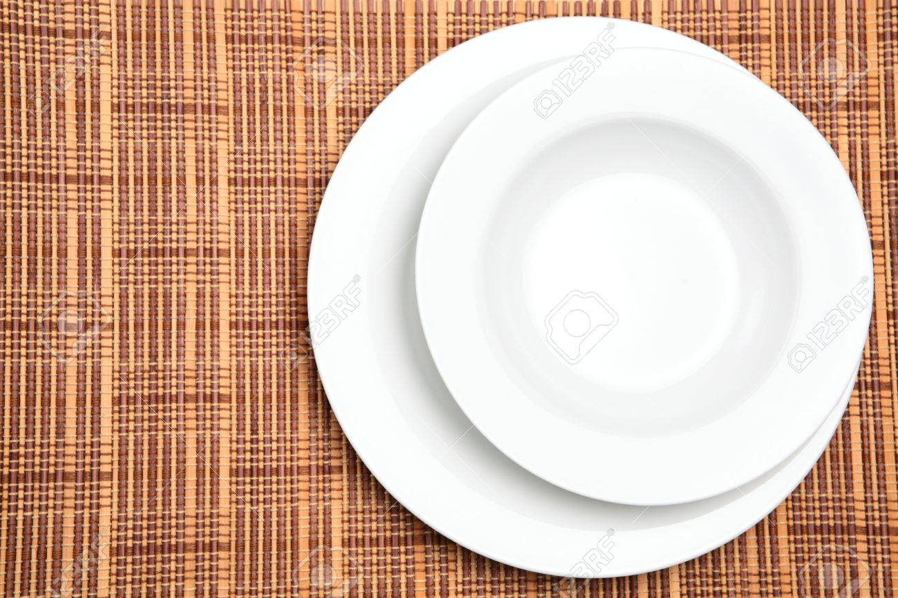 Stock Photo - Two white plates or dishes photographed over a wooden placement background with copy space on the left. & Two White Plates Or Dishes Photographed Over A Wooden Placement ...