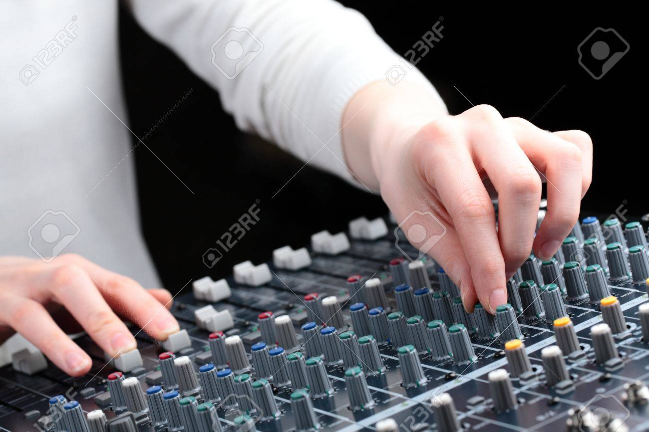An image of female hands adjusting the settings of an audio mixer